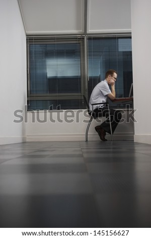 Full length side view of businessman using laptop in office - stock photo