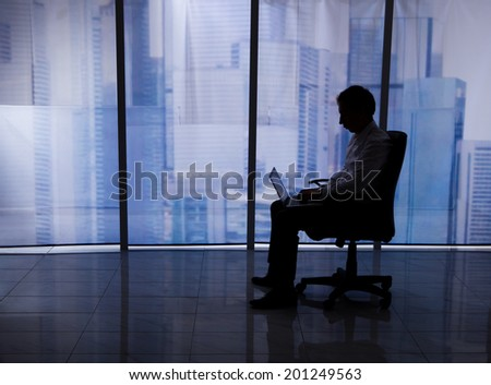 Full length side view of businessman using laptop on office chair by window - stock photo