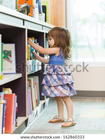 Full length side view of cute girl choosing book from school library - stock photo