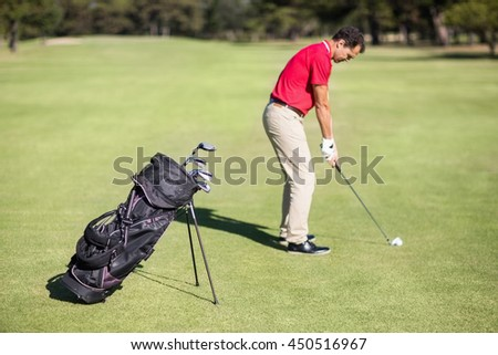 Full length side view of man playing golf while standing on field - stock photo
