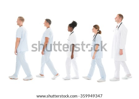 Full length side view of medical team walking in row against white background - stock photo