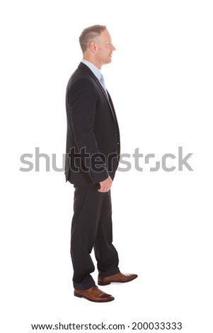 Full length side view of mid adult businessman standing isolated over white background - stock photo