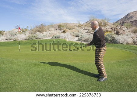Full length side view of senior male golfer swinging his club at golf course - stock photo