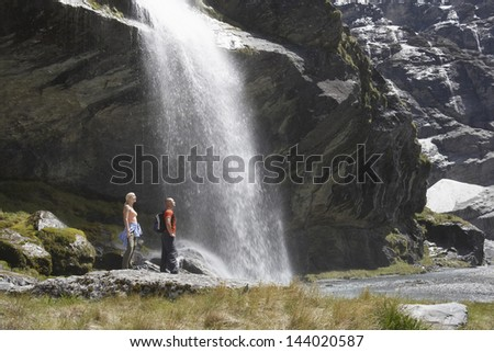 Full length side view of two hikers standing by waterfall at river - stock photo