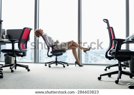 Full length side view of young businesswoman leaning back in chair at office - stock photo