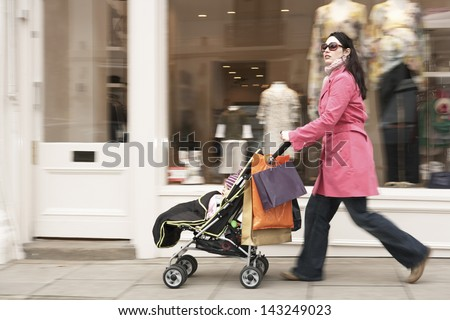 Full length side view of young mother pushing baby stroller by clothes shop - stock photo