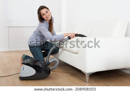 Full length side view of young woman vacuuming sofa at home - stock photo