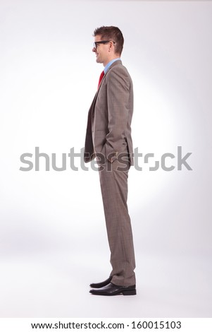 full length side view picture of a young business man with hands in pockets. on a gray background - stock photo