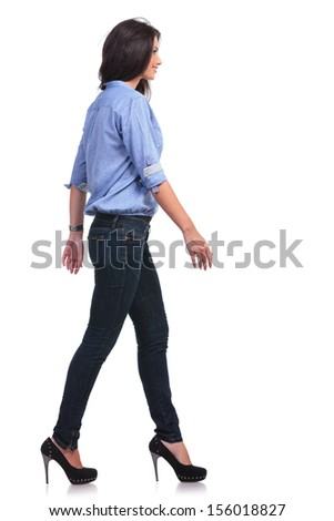 full length side view picture of young casual woman walking in front of the camera while looking forward. on white background - stock photo