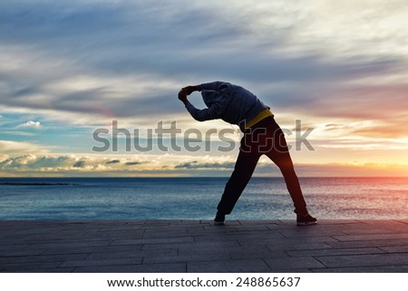 Full length silhouette portrait of a male jogger stretching in the morning and admiring amazing sunrise while standing next to the sea - stock photo