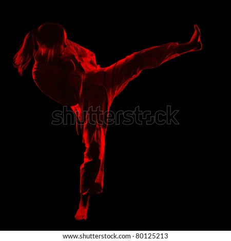 full-length silhouette portrait of beautiful martial arts girl in kimono excercising karate kata kick on black - stock photo