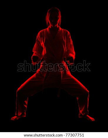 full-length silhouette portrait of beautiful martial arts girl in kimono excercising karate kata in kiba dashi pose on black - stock photo
