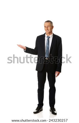 Full length smiling businessman holding copyspace. - stock photo