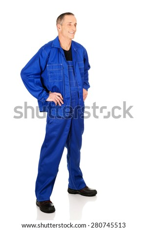 Full length smiling repairman with hands on hips. - stock photo