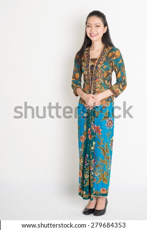 Full length Southeast Asian female in batik dress standing on plain background. - stock photo