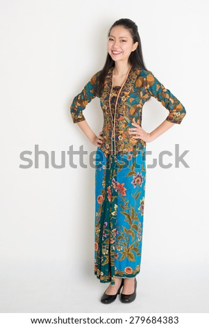 Full length Southeast Asian woman in batik dress standing on plain background. - stock photo