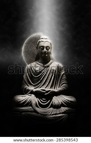 Full Length Stone Carved Seated Buddha Statue Dramatically Lit from Above on Dark Background, Meditation and Spirituality Concept Still Life Image - stock photo