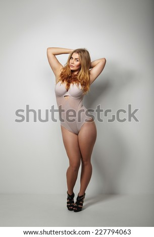 Full length studio image of beautiful voluptuous woman in body stockings standing on grey background. Sexy young plus size female model posing in underwear. - stock photo