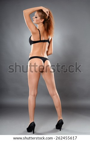 Full length studio portrait of a sexy lingerie model - stock photo