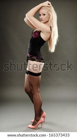 Full length studio portrait of alluring blonde wearing black lingerie and stockings - stock photo
