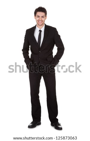 Full length studio portrait on white of a smiling confident young businessman standing with folded arms - stock photo