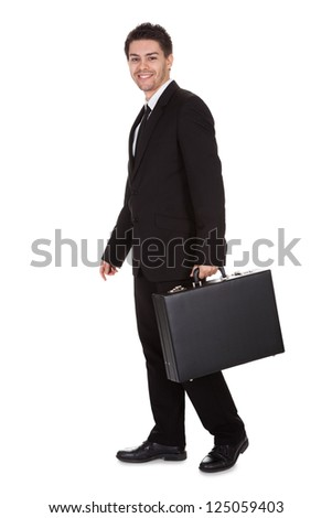 Full length studio portrait on white of a smiling confident young businessman standing with suitcase - stock photo