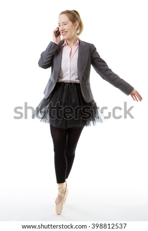 Full length studio shot of a business ballerina en pointe with a mobile phone raissed to her right ear.  isolated on white - stock photo