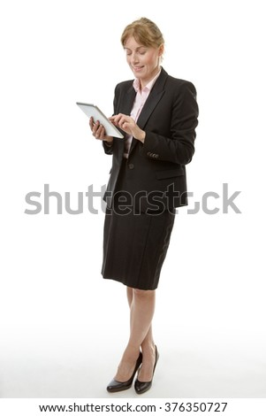 Full length studio shot of a mature business woman holding a tablet computer. isolated on white - stock photo