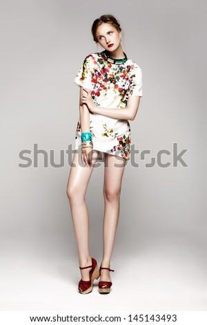 Full length studio shot of pretty model on grey background - stock photo