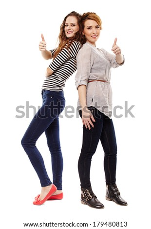 Full length studio shot of two girlfriends standing back to back and making the thumbs up sign isolated over white background - stock photo