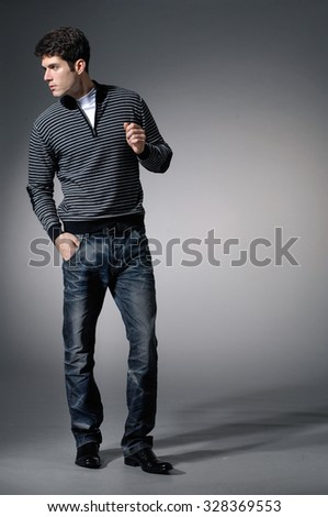 full length Stylish young man posing on light background - stock photo