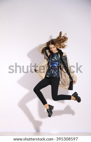 Full length The young long-haired girl jumping in studio. Beige coat. - stock photo