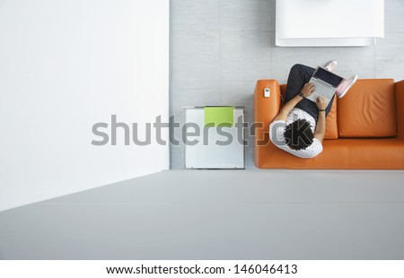 Full length top view of a man using laptop on orange sofa in reception room at office - stock photo