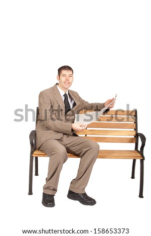 Full length, uncropped shot of a professional white collar worker sitting on a park bench reading a newspaper. Isolated on white. - stock photo