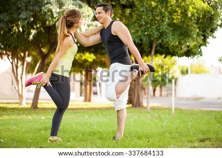 Full length view of a young couple stretching their legs and warming up together before exercising at a park - stock photo