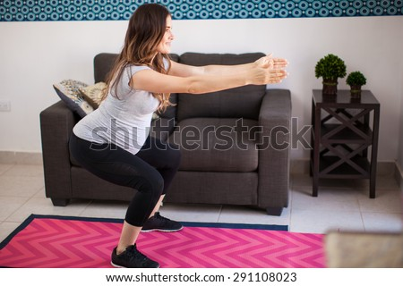 Full length view of a young pregnant mother exercising and doing squats at home - stock photo