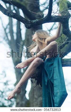 Full length view of one beautiful sensual sexy young mysterious woman with long lush hair in emerald dress sitting in forest on bare tree branches outdoor on natural background, vertical picture - stock photo
