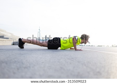 Full length view of strong build man with running armband doing push-ups on asphalt city road and listening to music with headphones,young male jogger warm up before start his workout training outside - stock photo