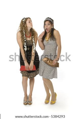Full length view of two teenage girls in fancy clothes with animated facial expressions. - stock photo