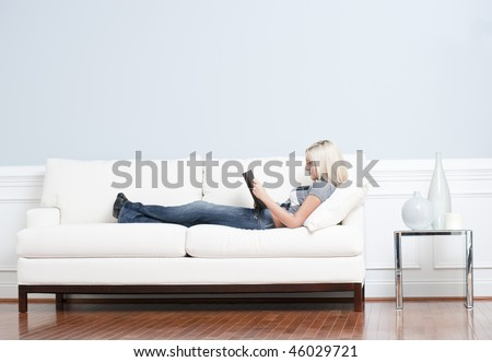 Full length view of woman reclining on white couch and reading a book. Horizontal format. - stock photo