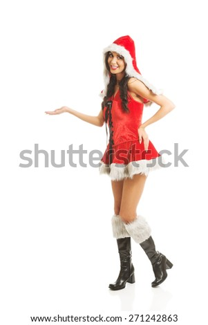 Full length woman holding something invisible in right hand wearing santa clothes . - stock photo