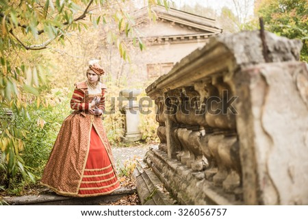 Full length woman in 16th century style red dress Young adult girl alone walk in autumn park Scary emotion on face Historical costume - Dress Spanish court elegant luxury lady - stock photo
