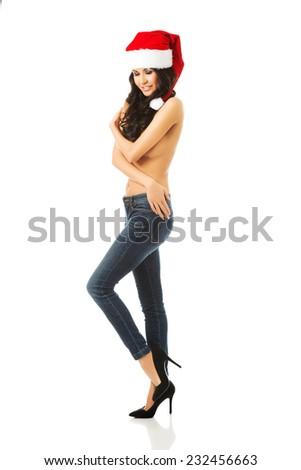 Full length woman shirtless wearing santa claus hat, looking at the camera. - stock photo