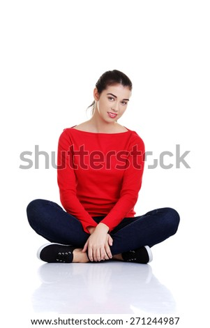 Full length woman sitting cross-legged on the floor - stock photo