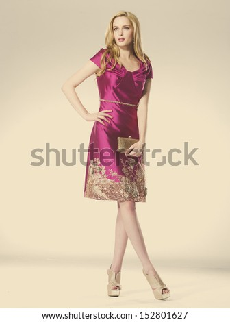 Full length young beautiful blond girl in elegant dress against gold background - stock photo