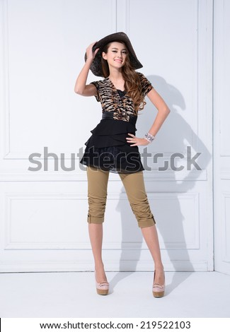 Full length young fashion model with hat posing standing  - stock photo