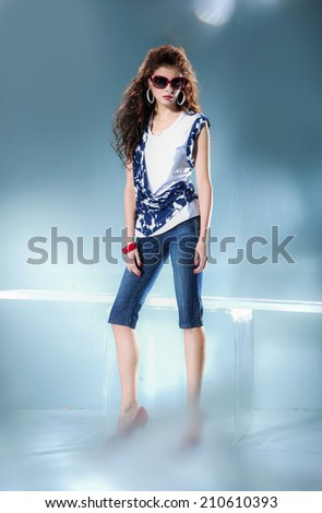 Full length young girl in fashion dress wearing sunglasses in light background - stock photo