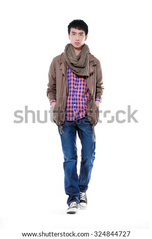 Full length young man standing with hands in pockets walking in studio - stock photo