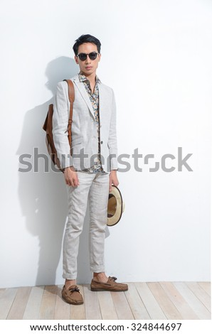 Full length Young man with bag, hat on wooden background - stock photo