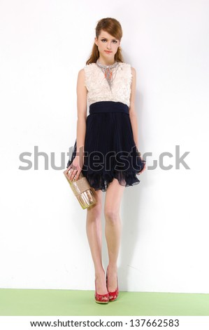 Full length young woman in elegant dress posing holding purse - stock photo